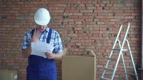 Porträt eines schlechten ausdrucksvollen männlichen Erbauers in Blättern einer arbeitenden einheitlichen Streuung stock video footage