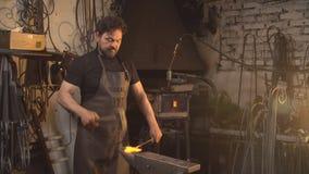 Porträt eines Schmiedes im Betriebsklima Ein Mann arbeitet mit flüssigem Metall in der Schmiede stock footage