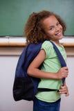 Porträt eines Schulmädchens, das ihren Rucksack zeigt Lizenzfreies Stockfoto