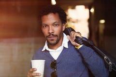 Porträt eines schwarzen Kerls der kühlen Reise, der mit Kaffee geht Stockbild
