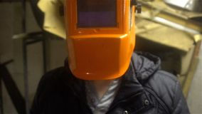 Porträt eines Schweißers, der vor der Kamera in einer orange Maske 4k steht Lizenzfreies Stockfoto