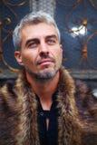 Porträt eines sexy Mannes im Wolfpelz und im dekorativen mittelalterlichen Fenster auf Hintergrund Stockfoto