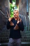 Porträt eines sexy Mannes und des Wolfs Pelz und der Adlerfedern Stockfoto