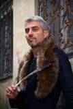 Porträt eines sexy Mannes und des Wolfs Pelz und der Adlerfedern und dekoratives mittelalterliches Fenster auf Hintergrund Lizenzfreie Stockfotos