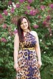 Porträt eines sinnlichen schönen Brunettemädchens mit dem langen Haar im gelb-schwarzen Kleid des Leoparden gehend in den Pa Stockbilder
