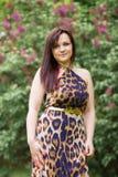 Porträt eines sinnlichen schönen Brunettemädchens mit dem langen Haar im gelb-schwarzen Kleid des Leoparden gehend in den Pa Stockfotos