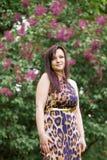 Porträt eines sinnlichen schönen Brunettemädchens mit dem langen Haar im gelb-schwarzen Kleid des Leoparden gehend in den Pa Lizenzfreies Stockbild