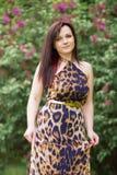 Porträt eines sinnlichen schönen Brunettemädchens mit dem langen Haar im gelb-schwarzen Kleid des Leoparden gehend in den Pa Lizenzfreie Stockfotos