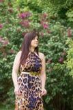 Porträt eines sinnlichen schönen Brunettemädchens mit dem langen Haar im gelb-schwarzen Kleid des Leoparden gehend in den Pa Stockfoto