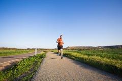 Porträt eines sportlichen jungen Mannes, der draußen in Natur läuft Lizenzfreies Stockfoto