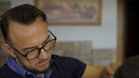 Porträt eines stilvollen Berufsfriseurs Vorlagenfrisuren bei der Arbeit in seiner Kabine stock video