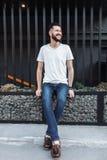 Porträt eines stilvollen Hippie Kerls, in einem weißen leeren T-Shirt, sitzen Lizenzfreie Stockfotografie