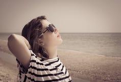 Porträt eines stilvollen Mädchens, das auf dem Strand sich entspannt Lizenzfreie Stockbilder