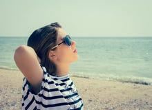 Porträt eines stilvollen Mädchens, das auf dem Strand sich entspannt Lizenzfreies Stockbild