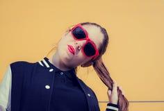 Porträt eines stilvollen Mädchens in der roten Sonnenbrille auf einem gelben backgro Stockbilder