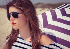 Porträt eines stilvollen Mädchens in einem gestreiften T-Shirt und in Sonnenbrille b Stockbild