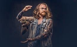 Porträt eines tattoed Rothaarigehippie-Mannes mit dem langen luxuriösen Haar und des Vollbarts gekleidet in ein T-Shirt und Jacke stockfoto