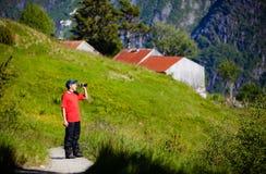 Porträt eines touristischen Kerls im roten Hemd, schauend durch bino Lizenzfreies Stockfoto