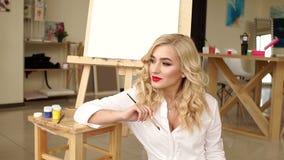 Porträt eines träumerischen Künstlers des jungen Mädchens im Studio für das Zeichnen Kunst stock footage