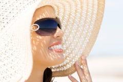 Porträt eines tragenden ein Sonnenbad nehmenden Hutes der Frau Stockfoto