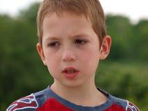 Porträt eines traurigen Jungen auf einem Hintergrund von Bäumen lizenzfreie stockbilder