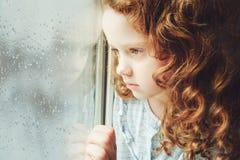Porträt eines traurigen Kindes, welches heraus das Fenster schaut Tonen des Fotos