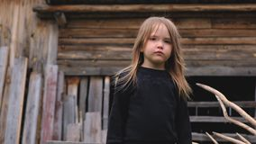 Porträt eines traurigen schönen kleinen Mädchens, das in einer schwarzen Strickjacke aufwirft stock footage