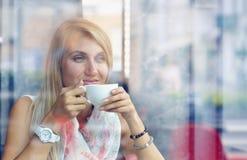 Porträt eines trinkenden Kaffees und draußen schauen des nachdenklichen Mädchens durch ein Fenster Stockfotografie