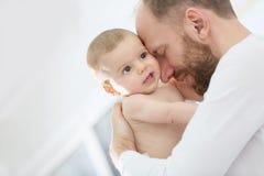 Porträt eines Vaters, der sein Baby streichelt Stockfotografie