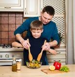 Porträt eines Vaters und seines Sohns, die einen Salat in der Küche zubereiten Stockbild