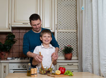 Porträt eines Vaters und seines Sohns, die einen Salat in der Küche zubereiten Stockfotos