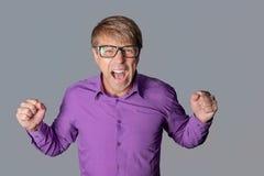 Porträt eines verärgerten Mannes mit Gläsern anstarrend entlang der Kamera, Showfinger und über grauem Hintergrund schreiend lizenzfreie stockbilder