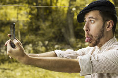 Porträt eines verrückten jungen Mannes mit der Kappe, die ein selfie nimmt stockfotografie