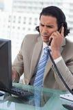 Porträt eines verwirrten Geschäftsmannes, der mit einem Monitor während arbeitet Lizenzfreie Stockfotografie