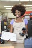 Porträt eines weiblichen Ladenangestellters des Afroamerikaners, der an der Kasse steht Lizenzfreies Stockfoto
