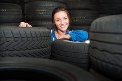 Porträt eines weiblichen Mechanikers, umgebene mit dem Auto Reifen Stockfotografie