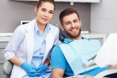 Porträt eines weiblichen Zahnarztes und des jungen Mannes in einem Zahnarztbüro stockbild