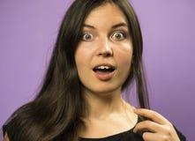 Porträt eines wundernden reizend Brunettemädchens auf einem purpurroten Hintergrund Stockbild