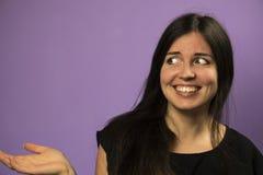 Porträt eines wundernden reizend Brunettemädchens auf einem purpurroten Hintergrund Stockfotografie