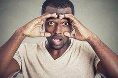 Porträt entsetzte jungen Mann auf grauem Wandhintergrund stockfotografie