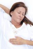 Glückliche reife Frau schlafend im Bett Stockfoto