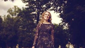 Porträt entspannter junger Dame in einer Sommerparkaufwartung Schönes junges Mädchen mit dem blonden gelockten Haar, Drehen im Fr stock video