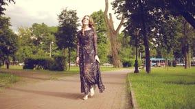Porträt entspannter junger Dame in einer Sommerparkaufwartung Schönes junges Mädchen mit dem blonden gelockten Haar, Gehen im Fre stock footage