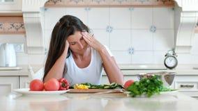 Porträt ermüdete die weibliche Hausfrau, die den rührenden Kopf der Kopfschmerzen hat, der Kreismassage beim Kochen macht