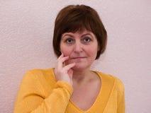 Porträt Frau der von mittlerem Alter mit der Hand nahe Gesicht Lizenzfreie Stockfotos