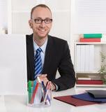 Porträt: Geschäftsmann, der in seinem Büro mit Anzug und Bindung sitzt lizenzfreies stockfoto