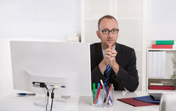 Porträt: Geschäftsmann, der in seinem Büro mit Anzug und Bindung sitzt lizenzfreie stockbilder