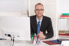 Porträt: Geschäftsmann, der in seinem Büro mit Anzug und Bindung sitzt stockfoto