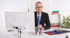 Porträt: Geschäftsmann, der in seinem Büro mit Anzug und Bindung sitzt stockbild
