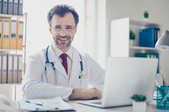 Porträt glücklichen erfolgreichen Doktors in den Gläsern, die am De sitzen lizenzfreies stockbild